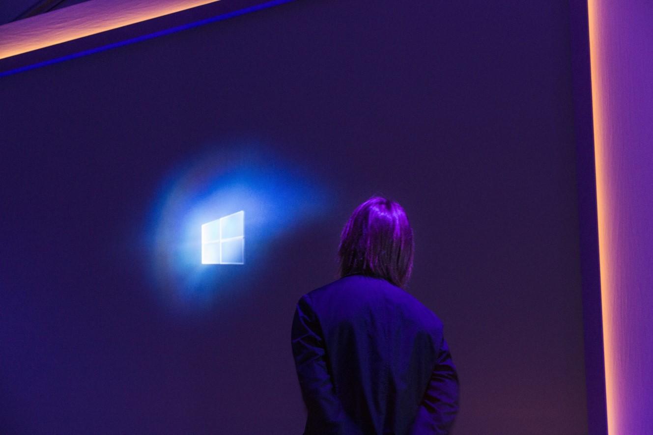 Mann steht vor einem großen Bildschirm, auf dem ein Sternenhimmel und ein weit entferntes Windows-Logo zu sehen ist.