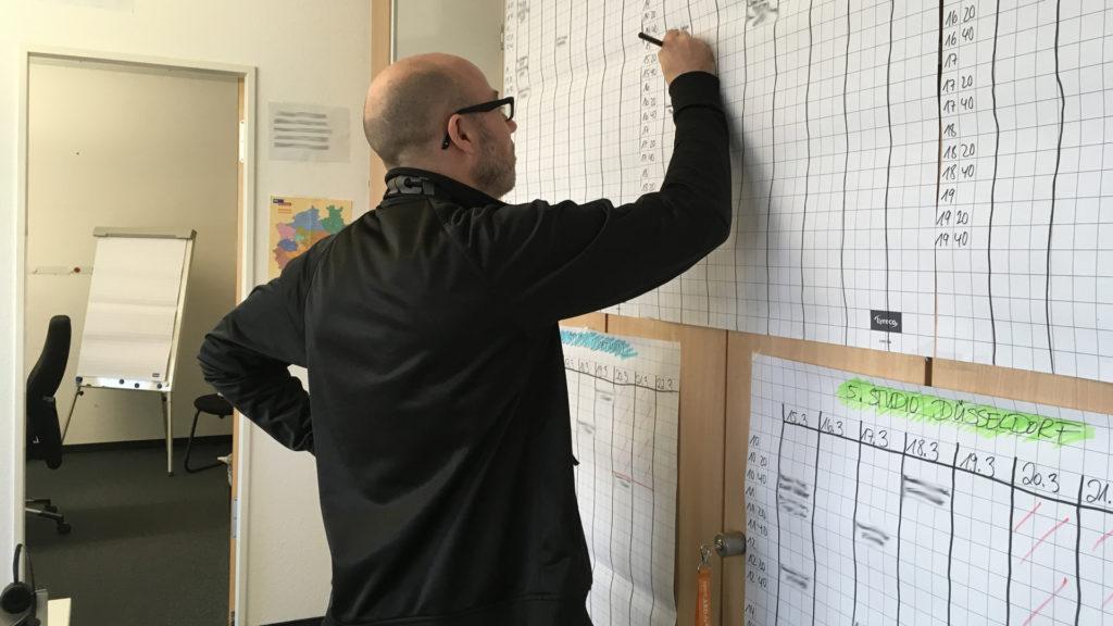 Eine Mitarbeiter der Ihre Wahl-Redaktion schreibt etwas an eine Wandliste.