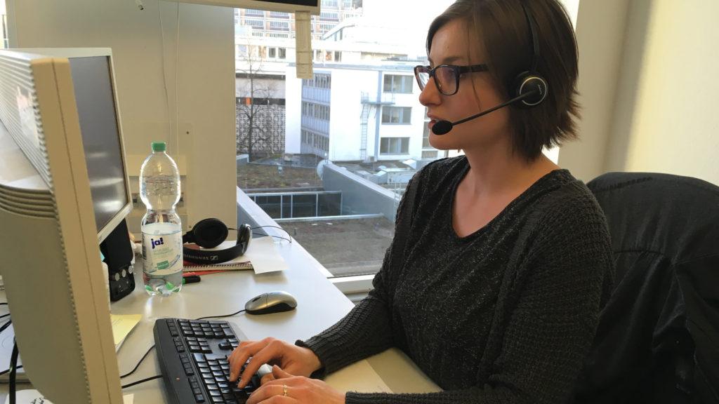 Eine Mitarbeiterin mit Headset am Arbeitsplatz.
