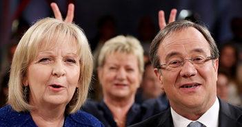 Silvia Lörhmann macht mit ihren Fingern den Kollegen Kraft und Laschet Hasenohren