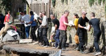 Mit einer Menschenkette befördern Helfer Sandsäcke in ein brüchiges Uferteil der Erft.